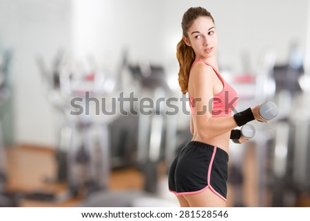 Woman working out with dumbbells at a gym - stock photo