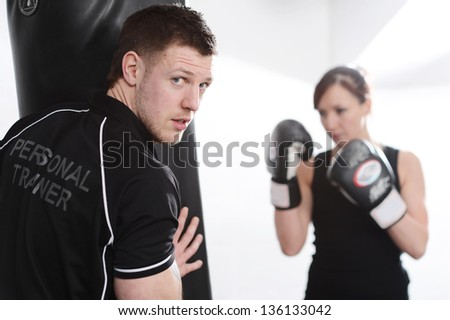 Woman working out with personal trainer on punch bag in gym - stock photo