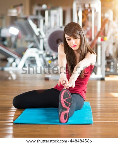 Woman working outs in a gym. Lens flare effect - stock photo