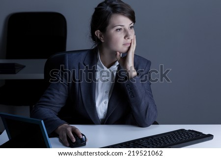 Woman working overtime in the office - stock photo