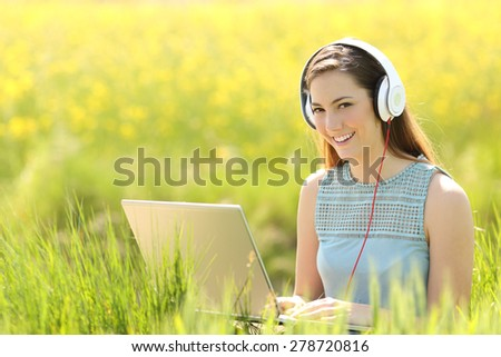 Woman working with a laptop and headphones in a field looking at camera - stock photo