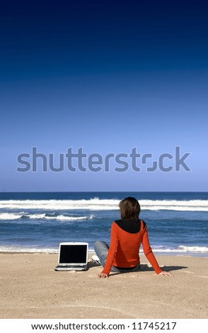 Woman working with a laptop on the beach - stock photo
