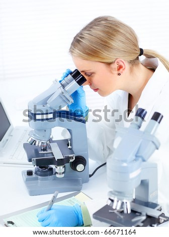 Woman working with a microscope in Laboratory - stock photo