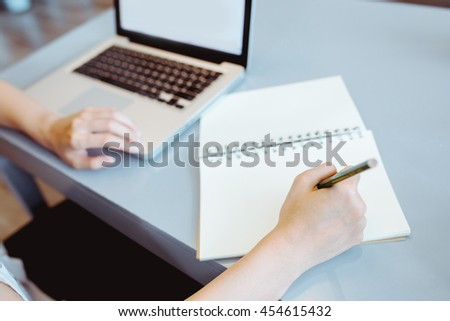 woman working with laptop and writing on notebook page (vintage tone)