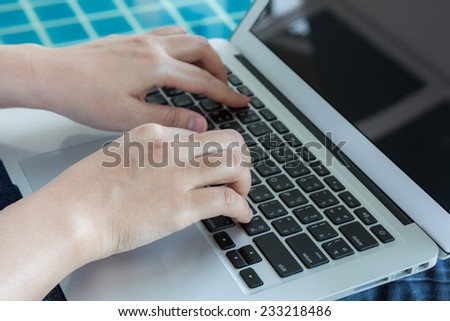 Woman working with laptop computer sitting at swimming pool - stock photo