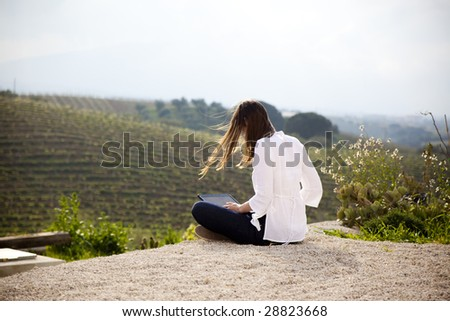 woman working with laptop in the countryside - stock photo