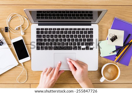 Woman working with laptop placed on wooden desk - stock photo