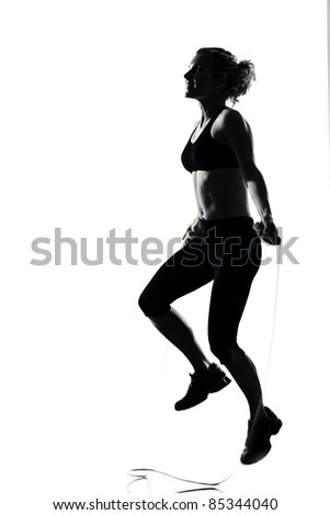 woman workout fitness posture body building jumping rope exercise exercising on studio isolated white background - stock photo