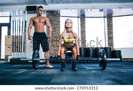 Woman workout with barbell and coach at gym - stock photo