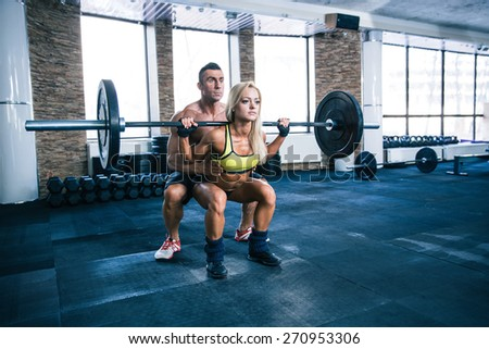 Woman workout with barbell and trainer at gym - stock photo