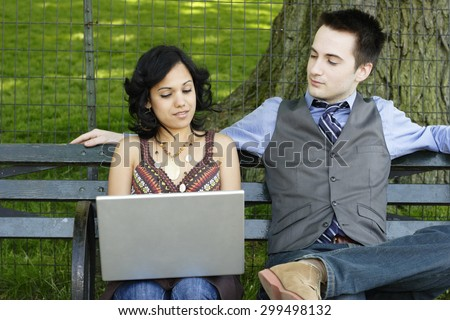Woman works on laptop as man watches. - stock photo