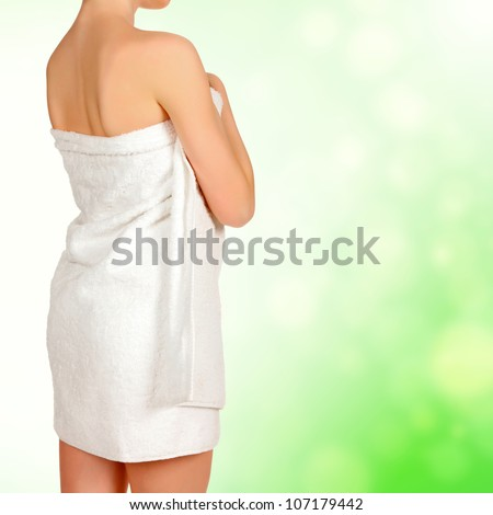 Woman wrapped in a white towel, green blurred background - stock photo