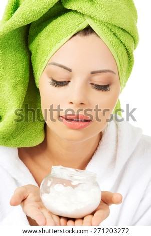 Woman wrapped in towel with cream container. - stock photo