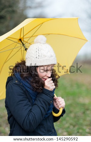 Woman wrapped up warmly against the winter weather walking under an umbrella coughing from a seasonal cold and flu - stock photo