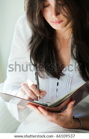 Woman writes on a paper - stock photo