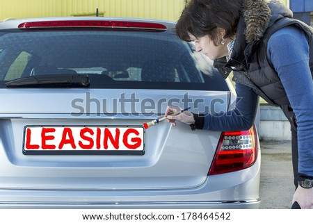 Woman writes with a brush on the sign of cars - stock photo