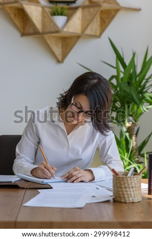 Woman writing at office during working day - stock photo