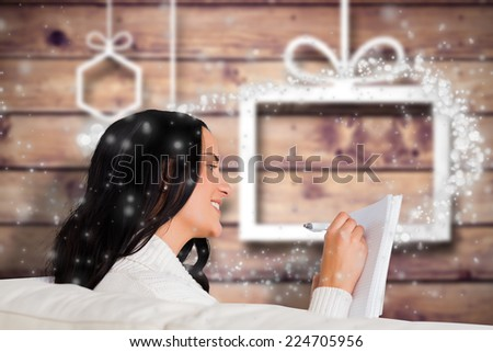 Woman writing down some notes against blurred christmas background - stock photo