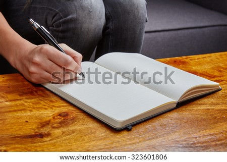 Woman writing in a book with a fountain pen