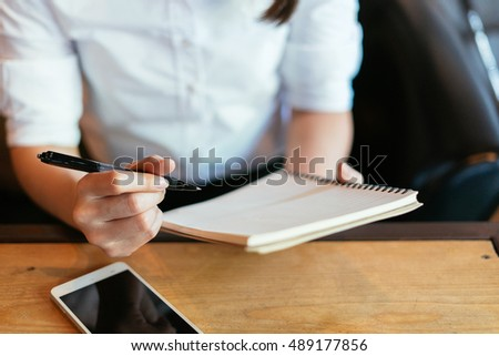 Woman writing in the notebook and drinking coffee.