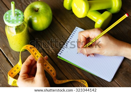 Woman writing nutrition diet and fitness workout routine. Healthy green detox, apple and dumbbells for slimming down concept. Female hands with measuring tape for checking weight loss. - stock photo