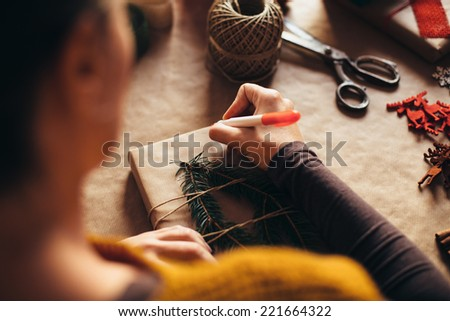 Woman writing on modern Christmas gifts presents at home - stock photo