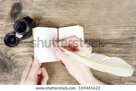 Woman writing on notebook - stock photo