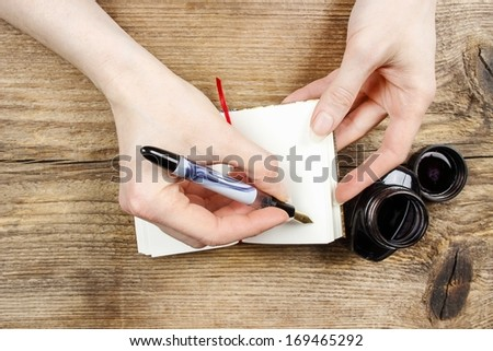 Woman writing on notebook. Wooden background - stock photo