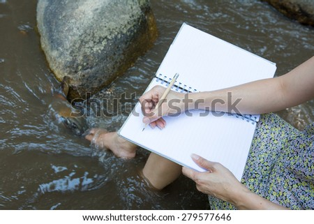 woman writing something in the notes pad while living on the stream  - stock photo