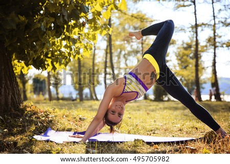 Woman Yoga - exercises in nature at the simmer autumn forest background