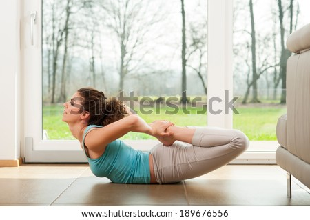 Woman yoga in front of the window - stock photo