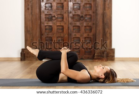 Woman yoga trainer in apanasana (knees to chest) pose - stock photo