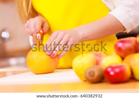 Woman young housewife in kitchen at home slicing fresh orange fruits on cutting board for salad or juicing. Healthy eating, cooking, raw food, dieting and people concept.