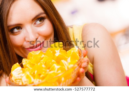 Woman young housewife in kitchen holds bowl full of sliced orange fruits preparing to make fresh juice or salad. Healthy eating, cooking, vegetarian food, dieting and people concept.