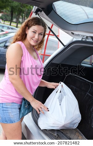 Woman young shopper on a car parking  - stock photo