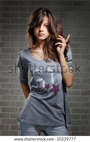 womanly brunette on brick wall background . Casual dress style - stock photo