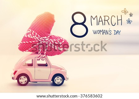 Womans Day message with miniature pink car carrying a heart cushion - stock photo