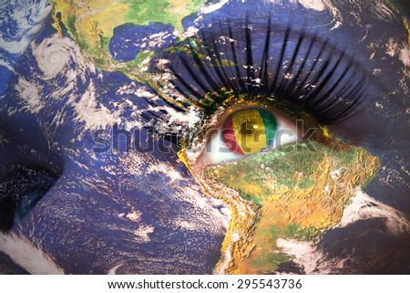 womans face with planet Earth texture and guinea flag inside the eye. Elements of this image furnished by NASA. - stock photo