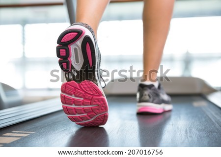 Womans feet running on the treadmill at the gym - stock photo