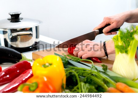 womans hand cutting vegetables with a big knife - stock photo