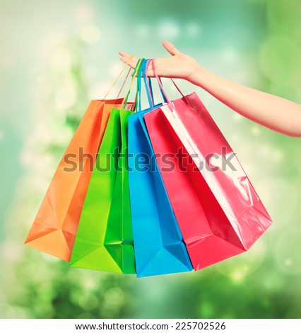 Womans hand holding a colorful shopping bags - stock photo