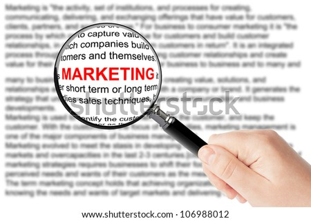 Womans hand, holding classic styled magnifying glass, with marketing word - stock photo