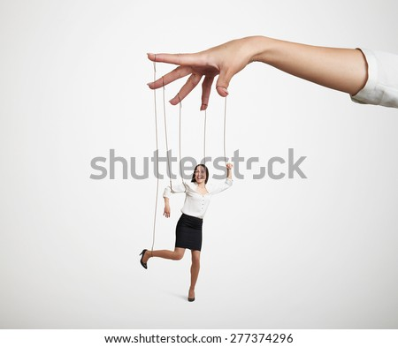womans hand manipulating the small puppet over light grey background - stock photo