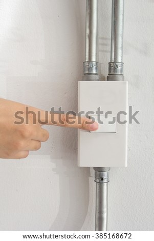 Womans hand with finger on light switch. Closeup of hand and switch only.  - stock photo