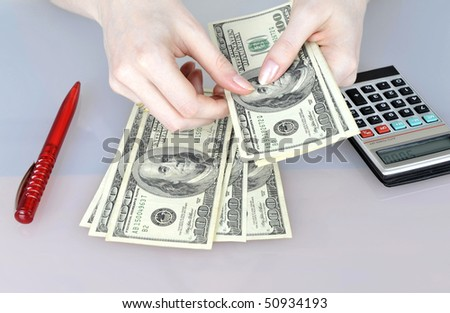 Womans hands counting $100 banknotes. - stock photo