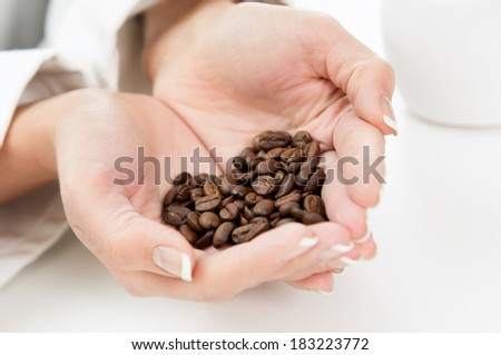 Womans Hands full of roasted coffe beans shaped as heart - stock photo