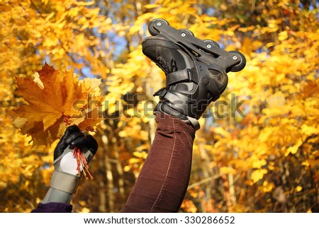 Womans leg in rollerblades and hand with yellow maple leaves in front of golden trees