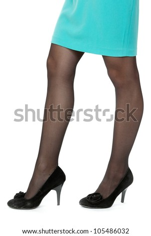 Womans legs wearing a short pinstripe skirt and black high heel shoes, on a white background. - stock photo