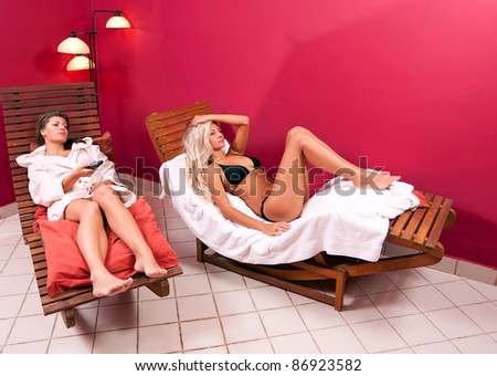 womans sitting in a relaxing chairs in the spa center and watching tv - stock photo