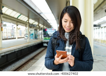 Womanuse of cellphone at train platform